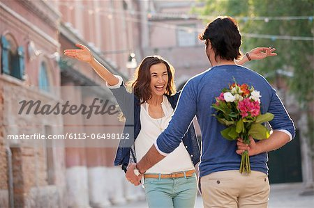 6113-06498162 © Masterfile Royalty-Free Model Release: Yes Property Release: No Enthusiastic woman approaching man with flowers behind back